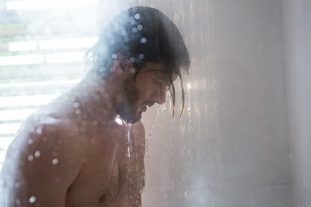Man taking a shower in bathroom
