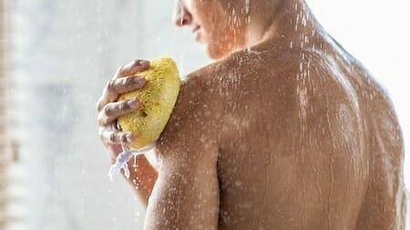Man cleansing himself in shower using yellow sponge