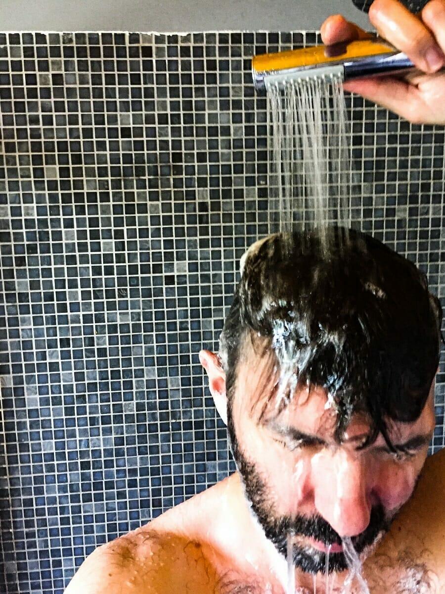 Man taking a shower using hand shower